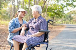 personne agée en fauteuil avec une professionnelle de l'autonomie